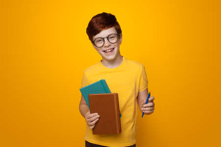 Young ginger schoolboy holding some folders is smiling on a yellow studio wall while wearing glasses and casual t-shirt