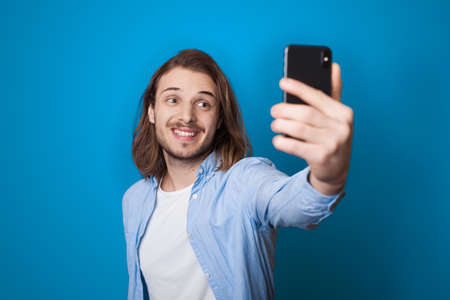 Young long haired man with beard is smiling and making a selfie using a phone on a blue studio wall in casual clothes 版權商用圖片