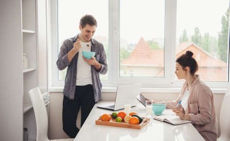 Charming couple eating cereals with milk and doing online lessons using tablet and laptop