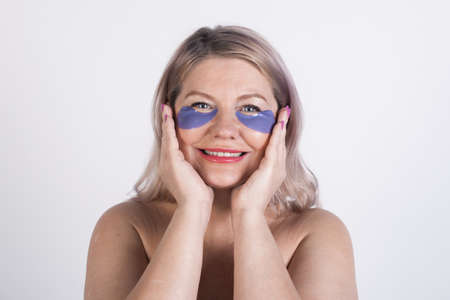 Close up photo of a caucasian woman wearing hydrogel eye patches and smile at camera with naked shoulders on a white studio wall