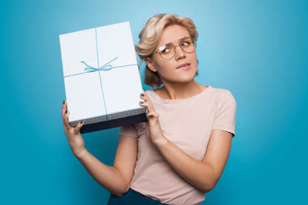 Blonde caucasian woman listening to her present gesturing impatience on a blue studio wall Stock Photo