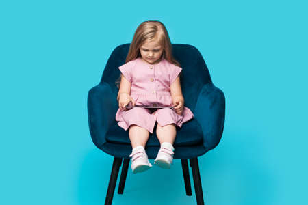 Concentrated caucasian girl is using a tablet while posing isolated on a blue studio wall in an armchair