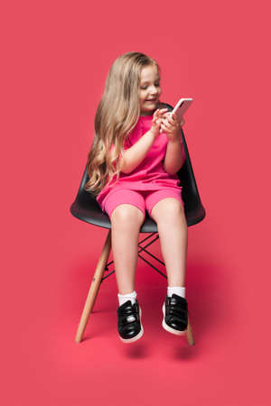 Blonde caucasian girl is sitting in a chair and smile using a phone ona red studio wall