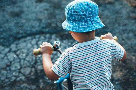 Upper view photo of a caucasian boy riding the bike and wear a hat in a summer day Standard-Bild