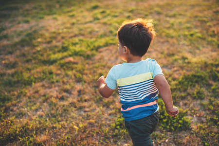 Upper view photo of a caucasian boy playing and running on a field during a summer evening Stok Fotoğraf