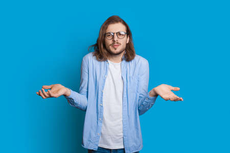Confused caucasian man with beard and long hair is posing indecisive while gesturing with palms on a blue studio wall