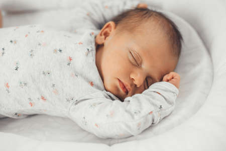 Close up photo of a sleeping baby in warm clothes with black hair feeling safe in his own bed