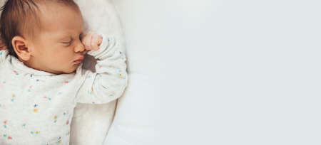 Upper view photo of a newborn baby sleeping well in bed near free space