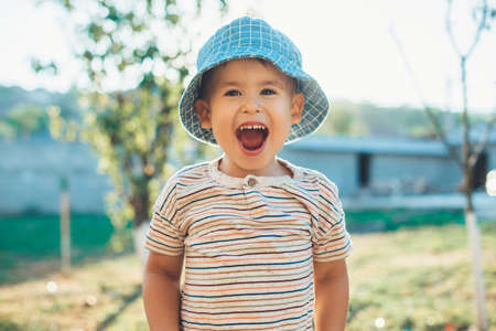Happy caucasian boy in a blue hat is laughing at camera while playing in the backyard of the house