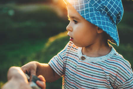 close up photo of a caucasian small boy with a blue hat taking something from his parents hand while playing in a field 免版税图像 - 157997424
