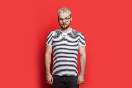 Serious blond caucasian man with beard and glasses is looking angry at the camera on red studio wall Foto de archivo