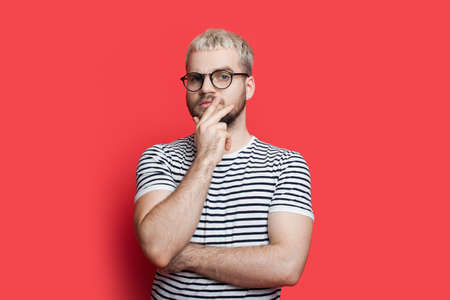 Blonde caucasian man with beard and glasses is posing thoughtful touching his chin on a red studio wall looking at camera 스톡 콘텐츠