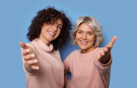 Close up photo of two women with curly hair smiling at camera and inviting gesturing with palms on a blue studio wall