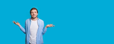Caucasian man with beard and long hair gesturing confusion on a blue wall with free space