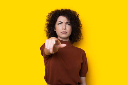 Sad curly haired woman is pointing at camera on a yellow wall gesturing unhappiness