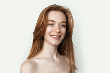 Ginger woman with freckles is massaging her face with a cream smiling with shoulders Imagens