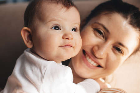 Close up photo of a freckled mother smiling proudly at camera holding her baby daughter