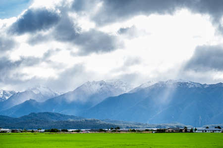 A stunning landscape scene of a rural area with green grassland cloudy snow mountain and sun rays after raining day.