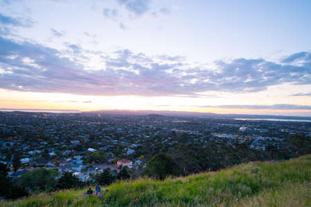 2018, DEC 3 - Auckland, New Zealand, A traveller couple enjoy beautiful view of a town in Auckland, New Zealand. Cloud sunset and town, View from Mt. Eden.