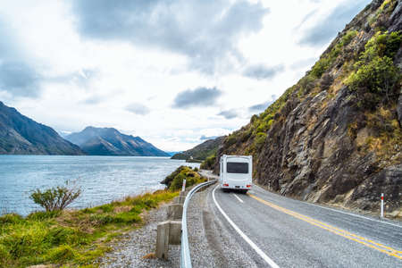 The stunning landscape of road beside the ocean with a cloudy and mountain scene. Standard-Bild