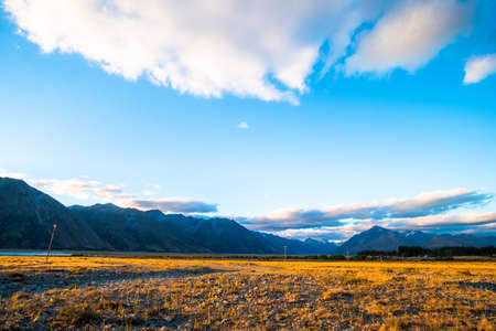Beautiful scene of the yellow grassland mt cook and lake tekapo before sunset. Stock Photo