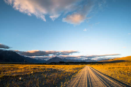 Beautiful scene of the road among the yellow grassland and the mountain beside lake Tekapo. Banco de Imagens