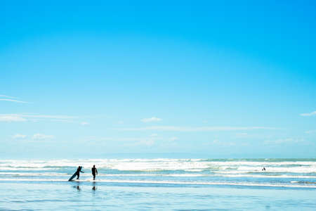 People enjoy their activities at the beautiful beach on a sunny blue sky day.