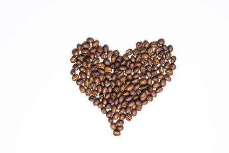 Flay lay style, Medium dark Roasted peaberry coffee beans with heart shape isolated on white background. coffee addict, coffee lover concept. 스톡 콘텐츠