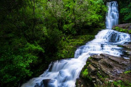 Long Exposure photography. Beautiful waterfall in the rainforest with green nature. Purakaunui Falls, The Catlins, New Zealand. Stock Photo - 102973685