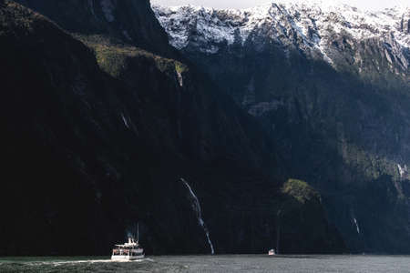 A stunning scene when a ferry cruising to a waterfall at Milford Sound, New Zealand. Stock Photo