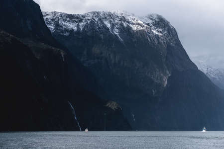 A stunning scene of nature with snow mountain and waterfalls at Milford Sound, New Zealand.
