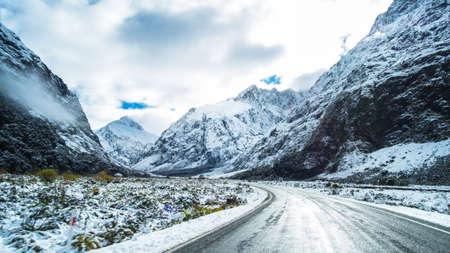 Lo scenario mozzafiato di una montagna rocciosa e alberi coperti di neve bianca. Una strada per Milford Sound. Un filmato durante la guida. Archivio Fotografico