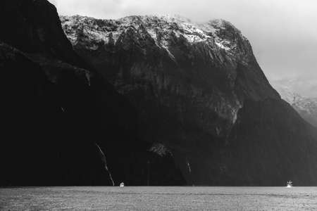 A stunning scene of nature with snow mountain and waterfalls at Milford Sound, New Zealand. Black and white photo.