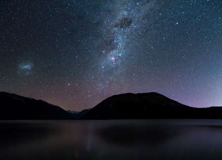 Amazing Starry night at Lake Rotoiti. Reflection of the Milky way and galaxy on the lake. Nelson Lake National Park, New Zealand. Фото со стока