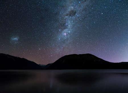 Geweldige sterrennacht aan het Rotoiti-meer. Weerspiegeling van de Melkweg en het sterrenstelsel op het meer. Nelson Lake National Park, Nieuw-Zeeland.