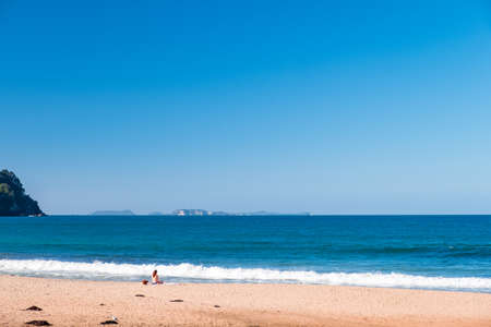 Ein Bikinimädchen, das Meditation tut und neben dem Ozean genießt. Friedliches Konzept..