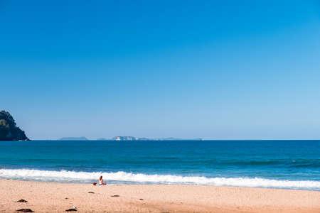 Una chica en bikini haciendo meditación y disfrutando junto al mar. Concepto pacífico.