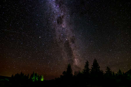 Oszałamiająca scena gwiaździstej nocy nad górą. Długa ekspozycja i wysoka czułość ISO..