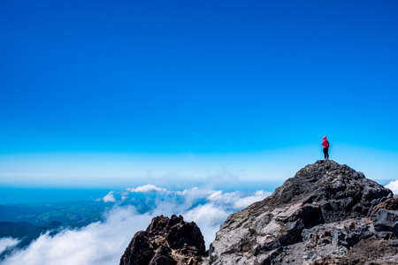 A person standing on the summit of the mountain. Beautiful view on a high mountain, blue sky and ocean. Stockfoto