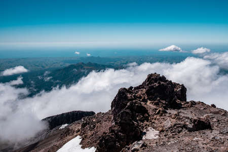 Panorama view above the clouds and forest from the summit of the mountain. Mount Taranaki, New Zealand.