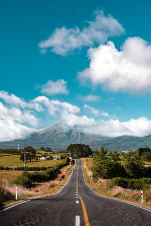 The beautiful view of Mount Taranaki covered with a cloud and fog after raining. Landscape in the rural area with Highway and beautiful nature. New Plymouth, New Zealand. Stockfoto