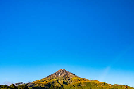 Landscape view of the Taranaki Volcano in the summer. Greenery scene of the mountain in the morning with blue sky.