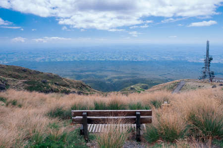 A bench on the hill with mountain and landscape view of the forest and blue sky.