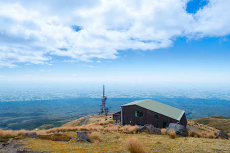 2019 February 11th, New Zealand, New Plymouth - A cell phone signal pole on a high mountain. Beautiful landscape scene with blue sky. Stockfoto