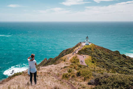 A female photographer is taking a photo Beautiful landscape scenery of the green mountain blue sky and the lighthouse, the heritage building. Cape Reinga, North Island, New Zealand.