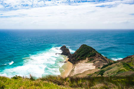 Beautiful landscape scenery of the green mountain, ocean and blue sky. North Island, New Zealand.