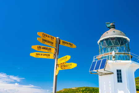 Cape Reinga, Northland, New Zealand. The white lighthouse and Yellow sign at the most northern of the country. Фото со стока
