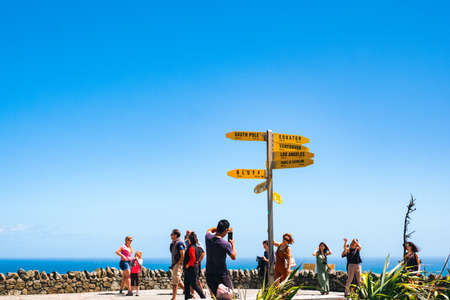 2019 February, 24th, New Zealand, Northland, Cape Reinga - People visit the heritage lighthouse and taking a photo with a yellow sign. The beautiful scenery of the landscape with ocean and blue sky. Редакционное