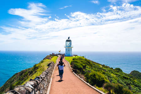 2019 February, 24th, New Zealand, Northland, Cape Reinga - People visit the heritage lighthouse and the most northern point in the country. The beautiful scenery of the landscape with ocean and blue sky.