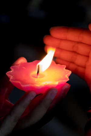 A hand holding a red candle and other hand shielded the wind. Ceremony and commemorate concept. Black background.